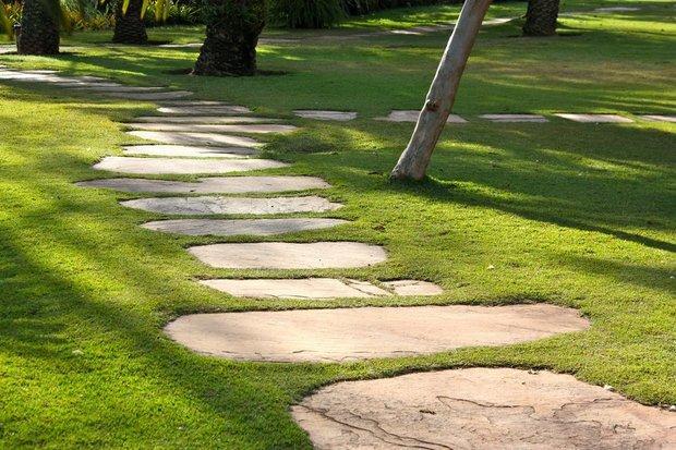 Эффектно смотрятся пошаговые дорожки из огромных плит набольших участках.