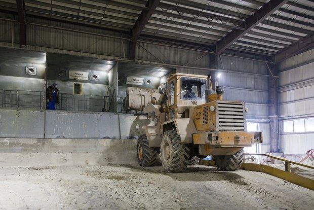 Фронтальный погрузчик загружает глину на промышленные весы на заводе Kerama Marazzi