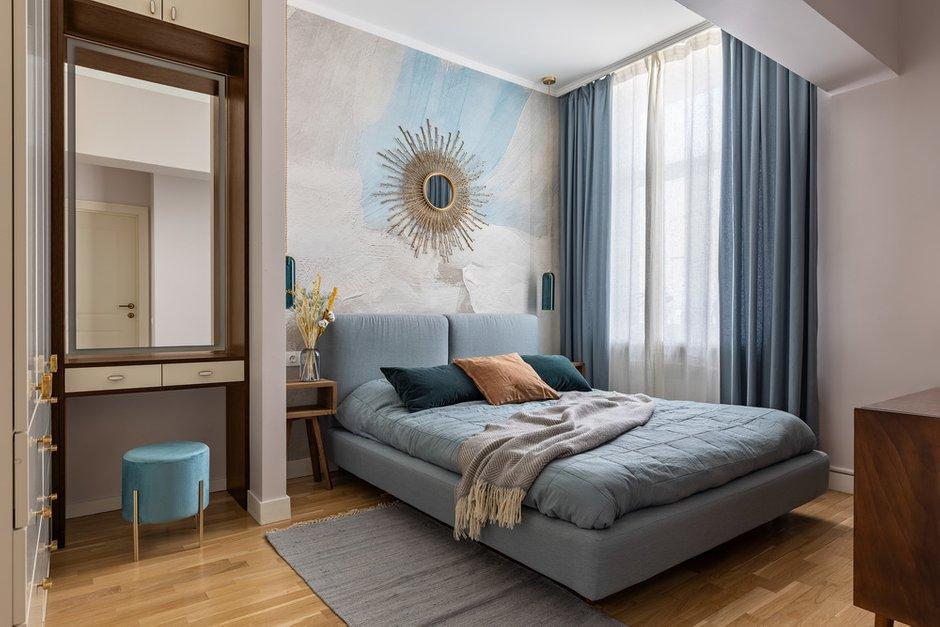 В спальне в изголовье кровати обои Affresco, а акцентом стало зеркало-солнце, как будто выглядывающее из облаков.