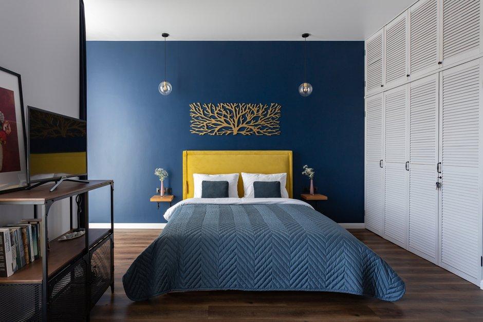 Кровать с обивкой яркого горчичного цвета — именно тот предмет, вокруг которого строился весь интерьер.