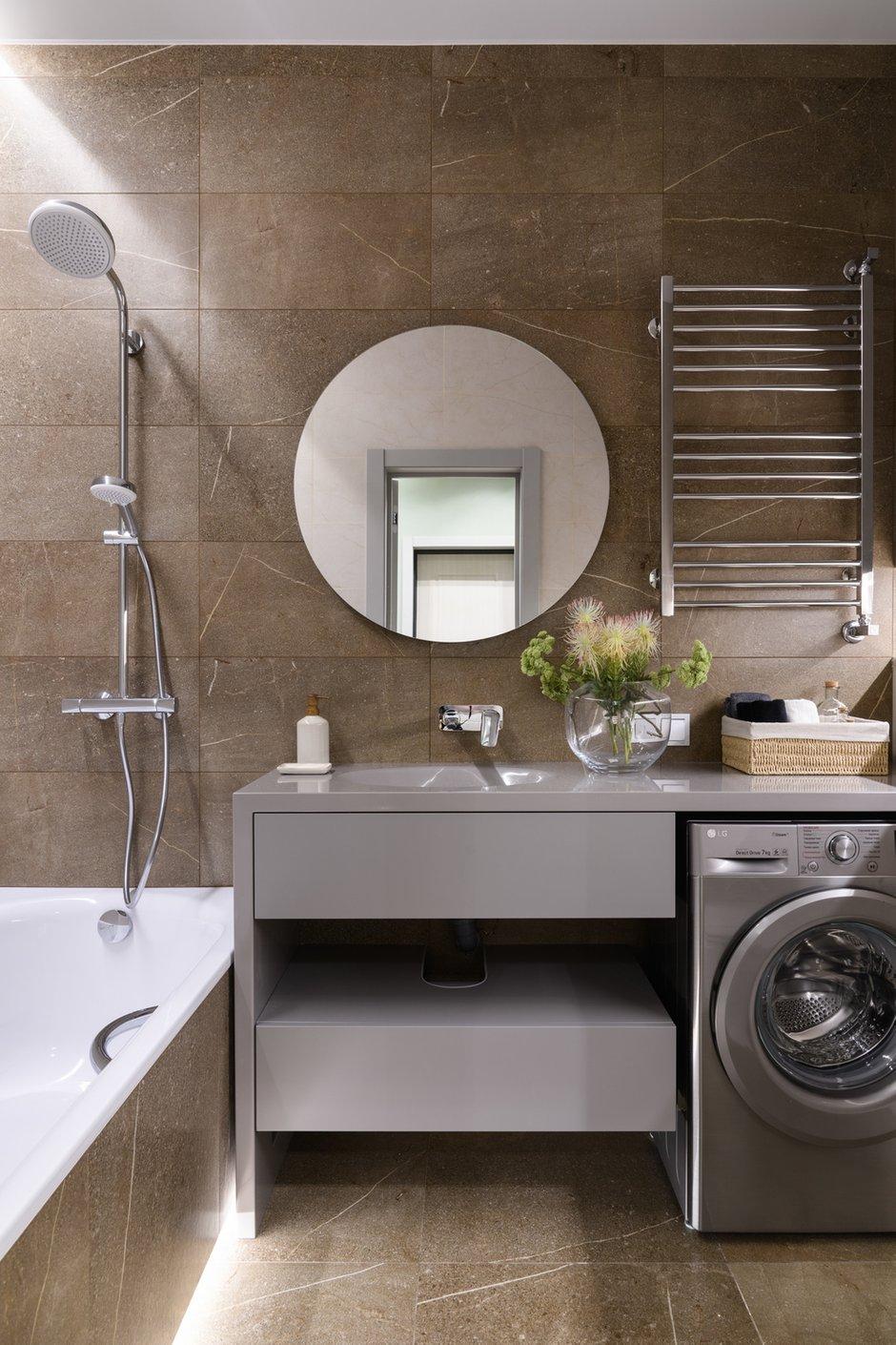 Ванная комната традиционно решена в керамической плитке сдержанных серо-коричневых оттенков.