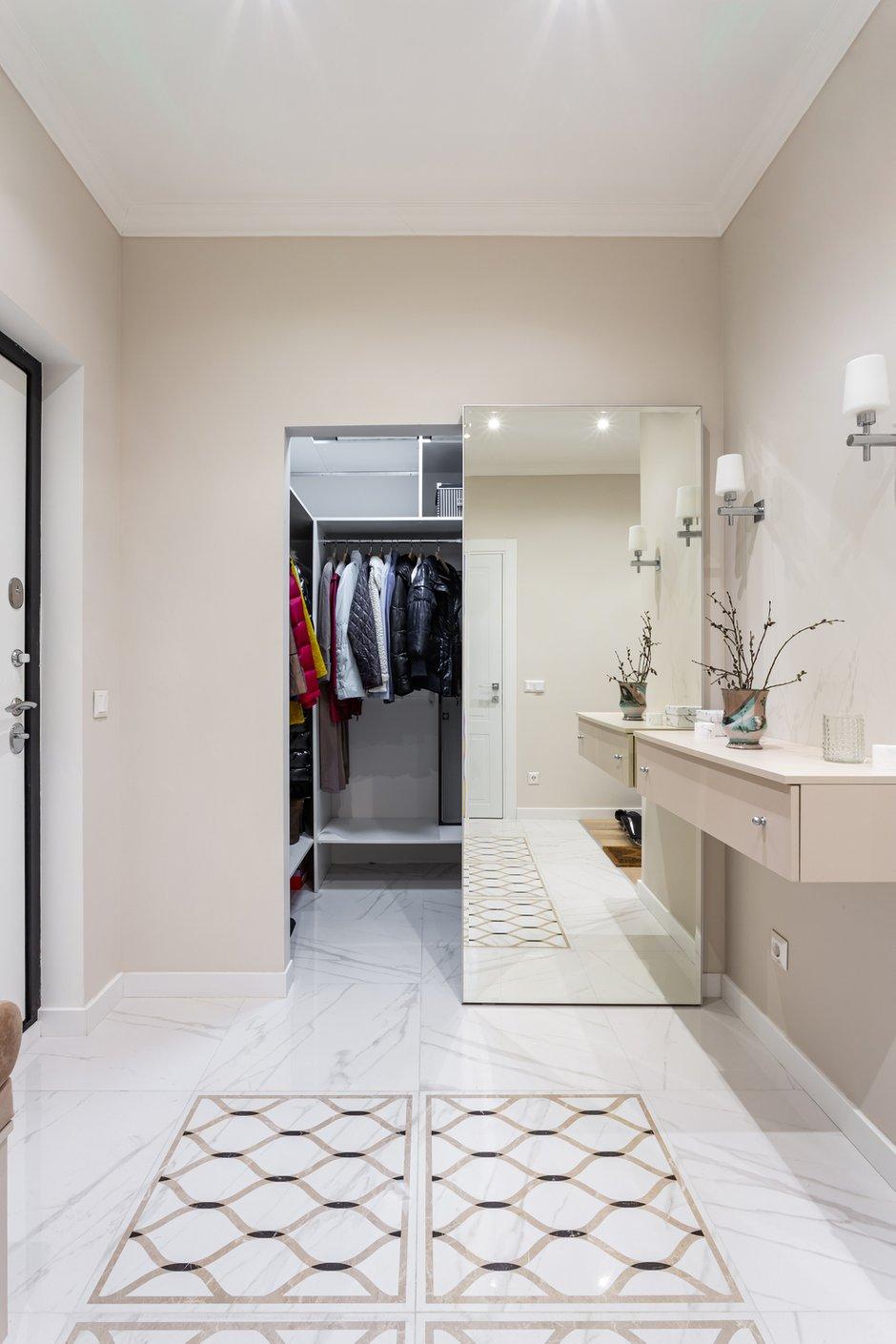 Гардеробную в прихожей спрятали за зеркальной дверью: она расширяет пространство и заменяет отдельно стоящее зеркало в пол.