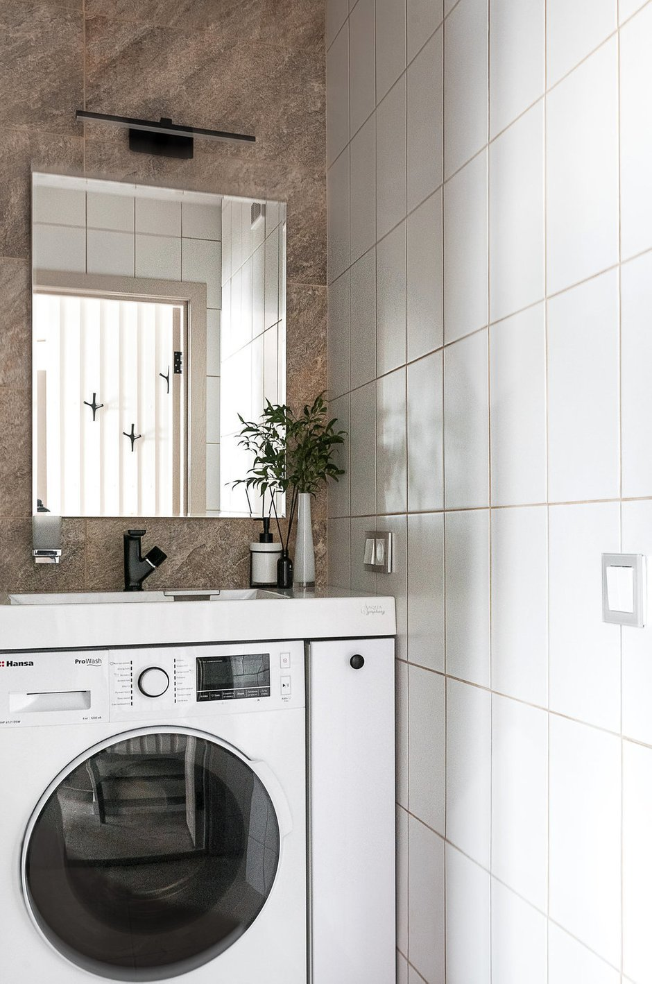 Часть стен — в темном керамограните, перекликающемся с текстурой камня на фартуке кухни, остальные стены — белые, чтобы не затемнять и зрительно расширить пространство помещения.