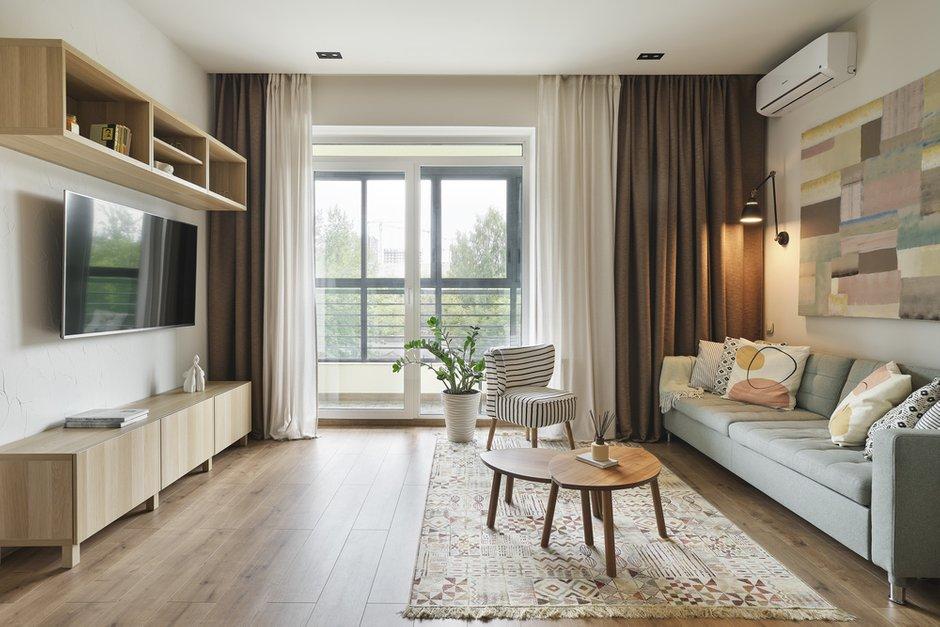 Вся мебель подбиралась на основе скандинавского стиля с элементами кантри. Так, в гостиной появилось маленькое кресло с полосатым принтом на ткани — под зебру. Столики в цвете орех, напоминающие Африку, и голубой диван, ассоциирующийся с небом. В зоне кухни деревянный круглый стол и стулья напоминают о дачных посиделках.
