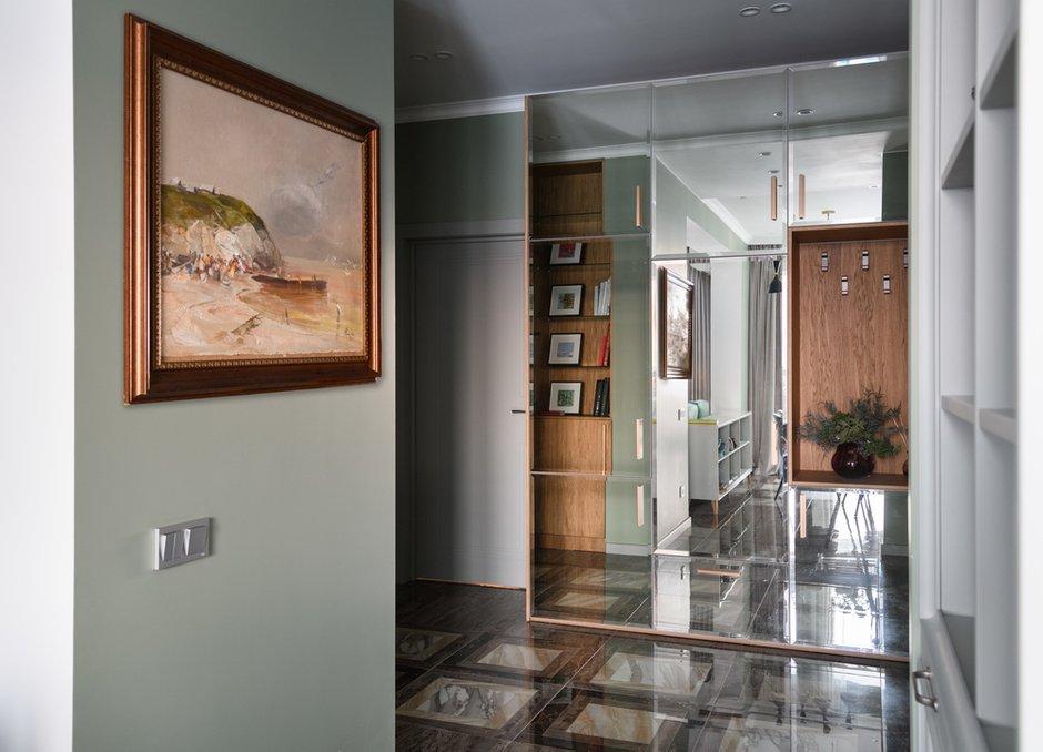 В прихожей находятся вместительный шкаф для сезонной одежды с зеркальными фасадами и встроенный стеллаж.
