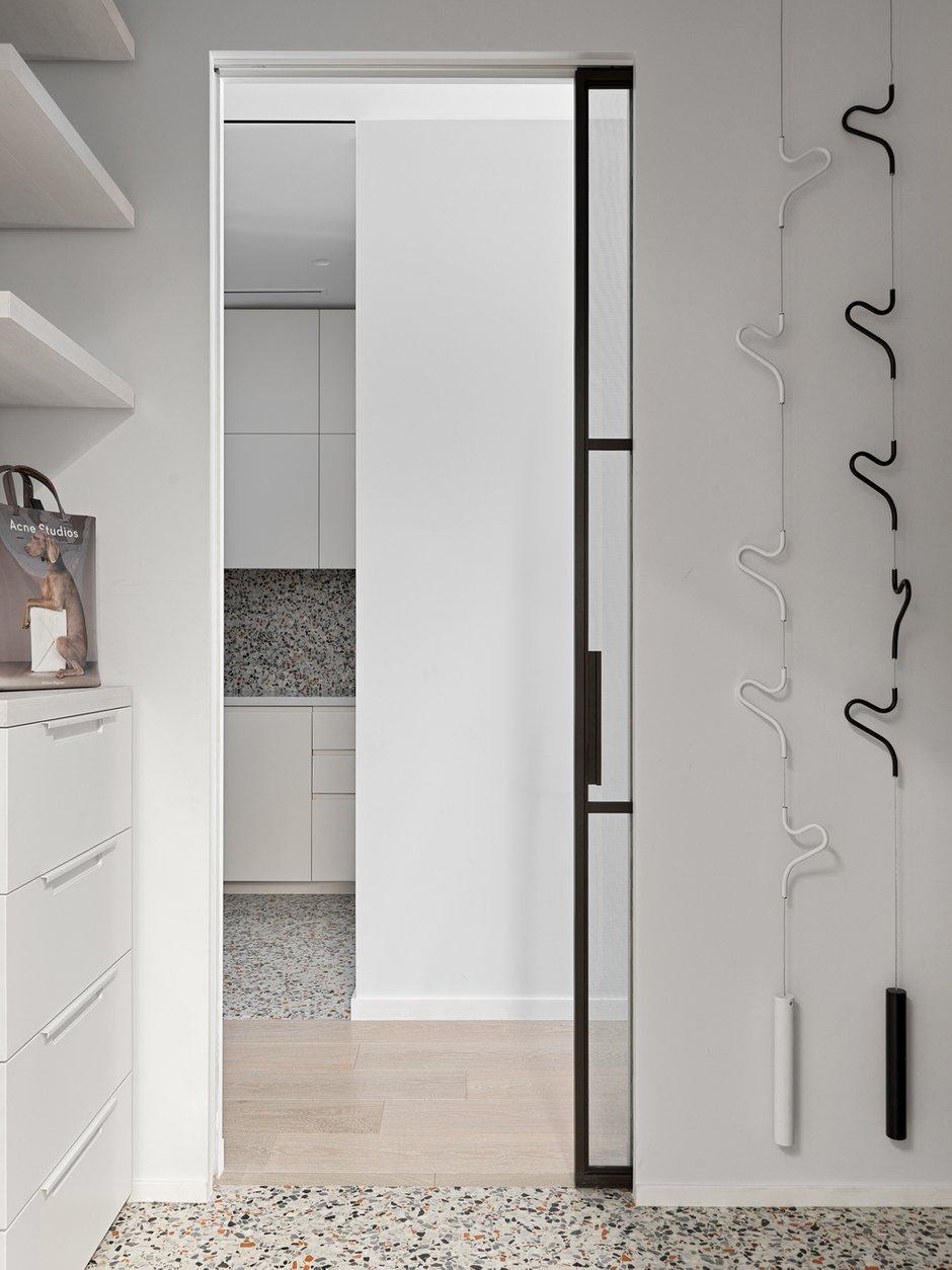 Система хранения крепится к полу и потолку, а не к стенам. Модули индивидуальной ширины, поэтому пространство задействовано максимально. Здесь же в прихожей находится миска для собаки.