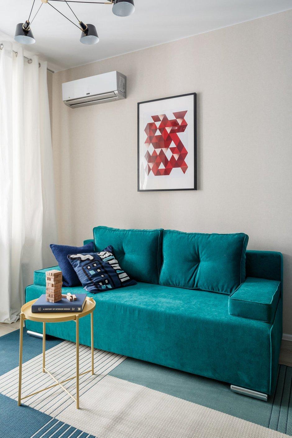 В гостиной в глаза бросается яркий изумрудно-зеленый диван — именно его обивка и привлекла дизайнеров.