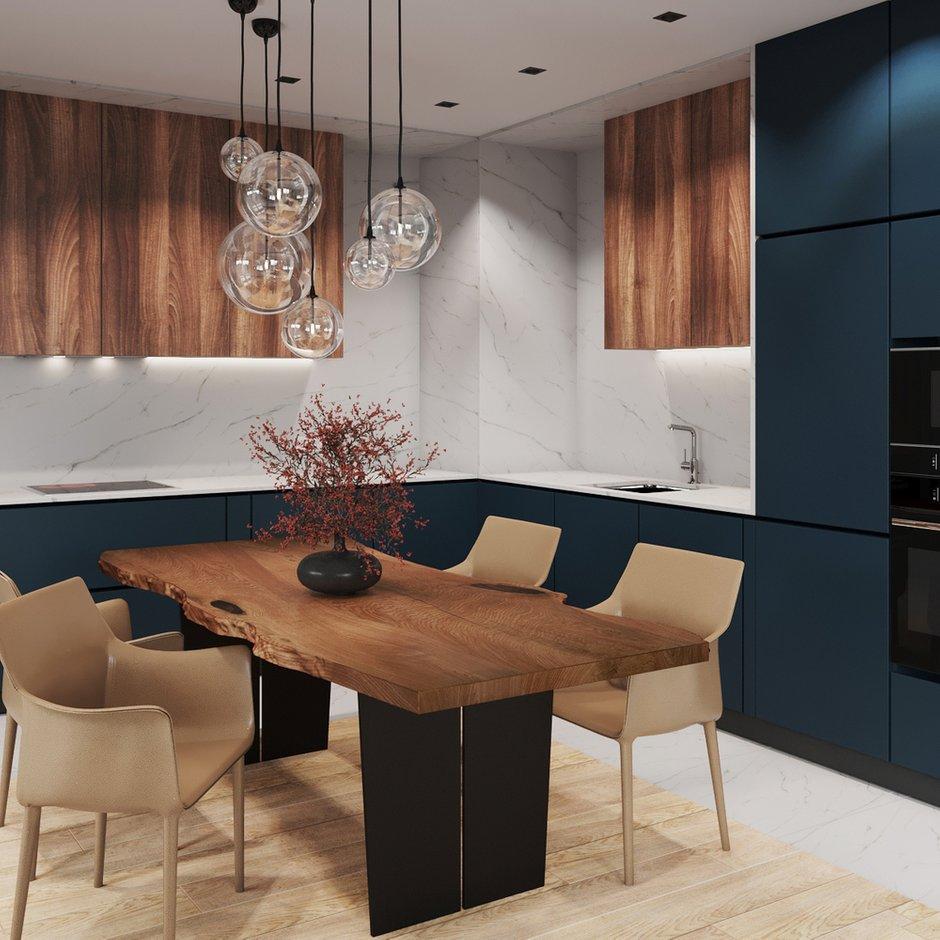В отделке кухни комбинировали темные матовые фасады и шпон дерева. А пространство между ними выложили керамогранитом под мрамор.