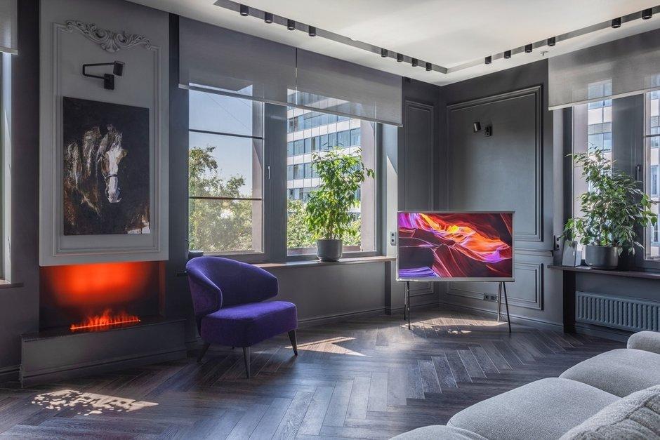 Напротив дивана разместили фиолетовое кресло, которое можно легко передвигать по комнате.