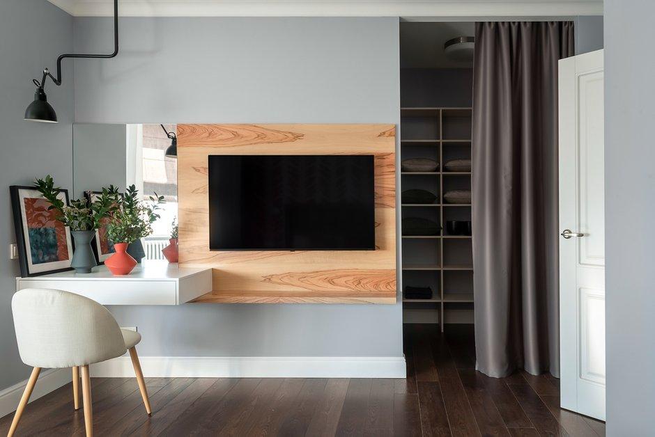Отдельного упоминания заслуживает декоративная панель для размещения телевизора, выполненная из экзотической древесины и совмещенная с зоной мейк-ап с хитрыми выдвижными ящиками, которые открываются просто нажатием на поверхность.