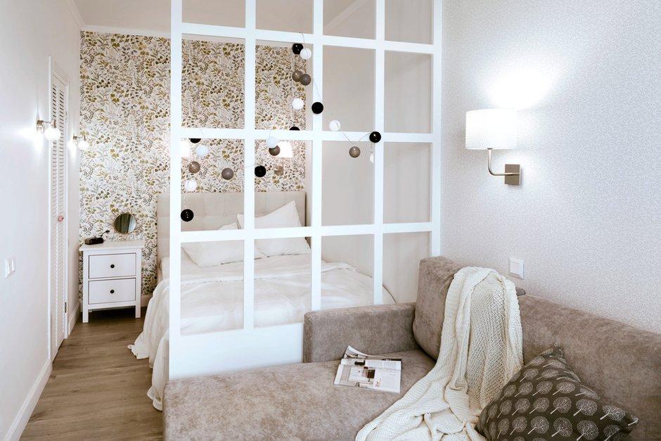 Зонирование в жилой комнате сделали при помощи перегородки из МДФ. Таким образом ограничили приватную зону — спальню. В изголовье кровати поклеили скандинавские обои с цветочным орнаментом — получилось очень уютно.