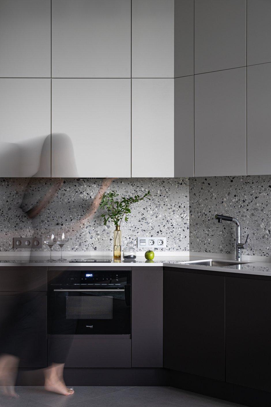 Покрытие фасадов — матовая бархатистая эмаль: выглядит очень стильно и минималистично, компенсируя незатейливую форму гарнитура. Столешница из искусственного камня, мойка из нержавеющей стали.