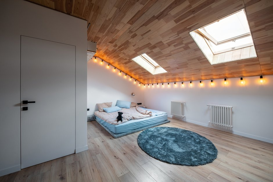 Мансардные откосы потолка отделаны вагонкой, а стык со стенами протянут обычным канатом — простая и уютная «изюминка» интерьера.