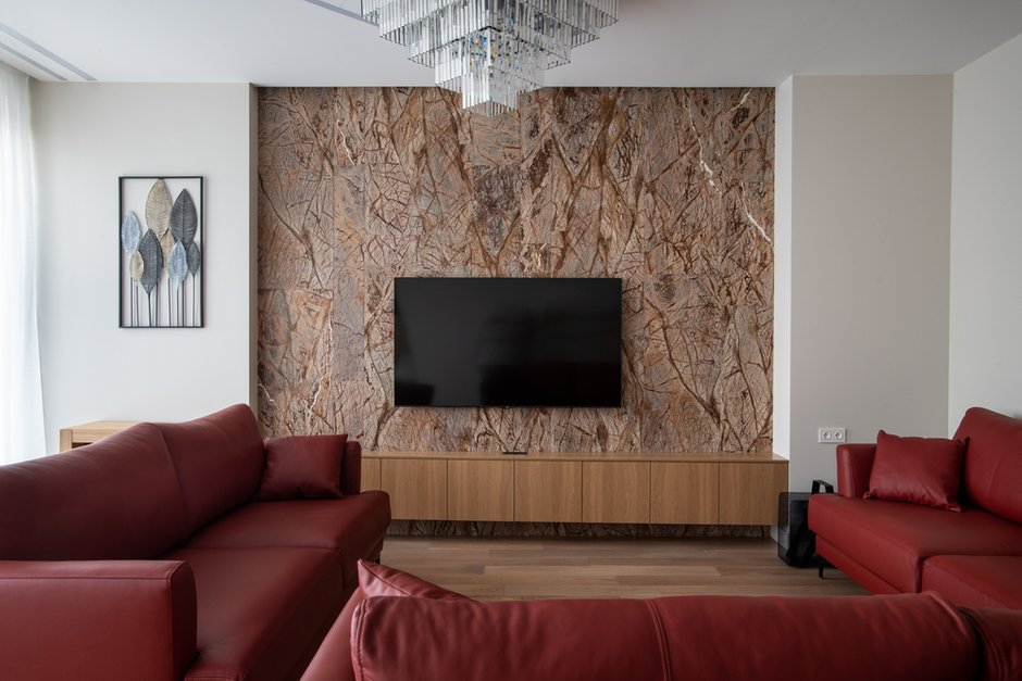 Диван специально искали в коже красного цвета и с наполнителем пух/перо. Слева от телевизора разместили раскладной вместительный стол-консоль от итальянского производителя.