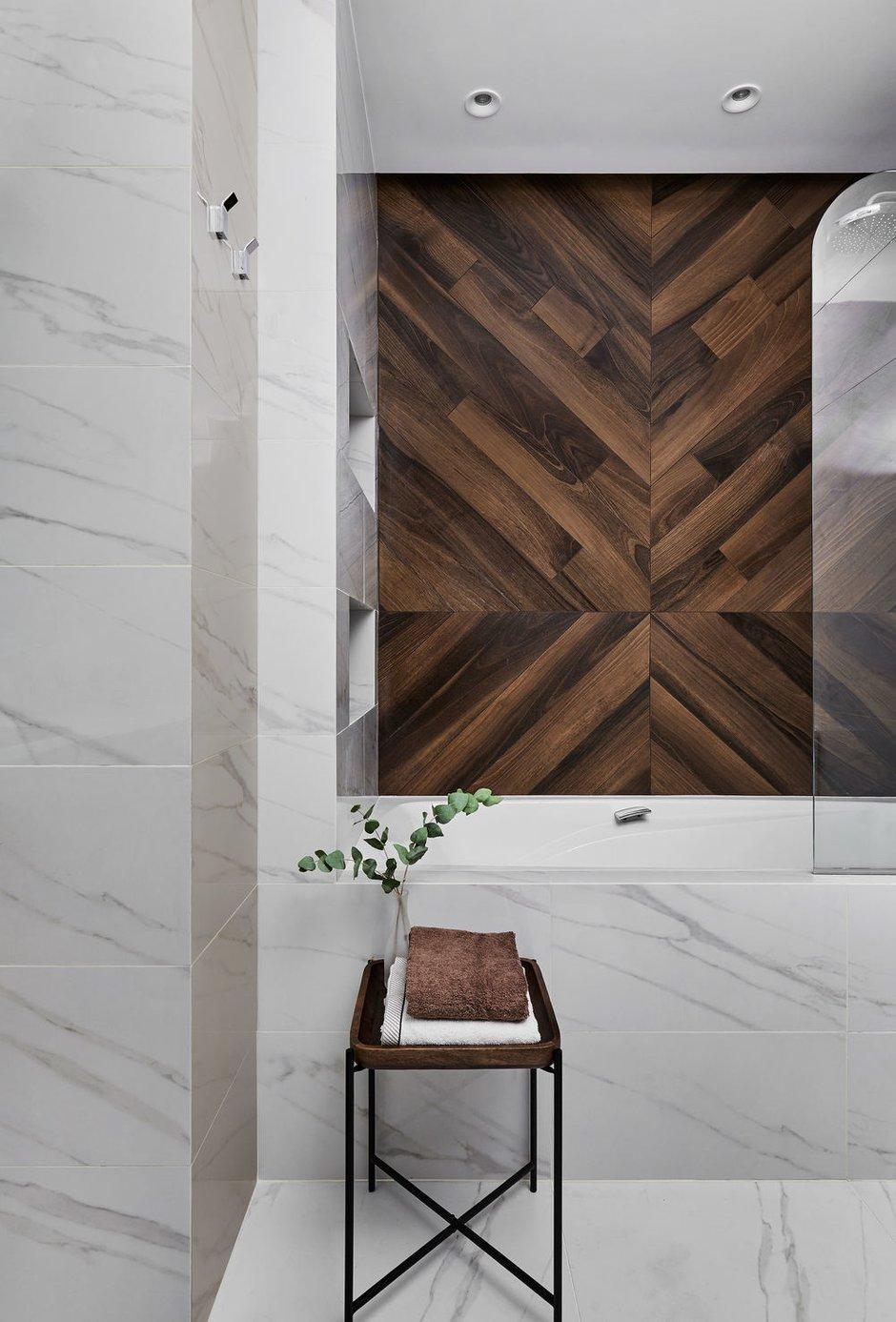 Плитку под орех также использовали в оформлении ванной комнаты, тем самым связав ее с остальным пространством квартиры и добавив законченности.