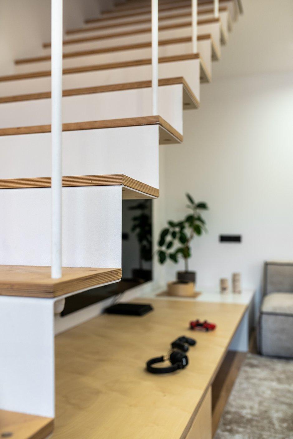 Сделанная на заказ лестница из листового металла ведет на второй этаж.