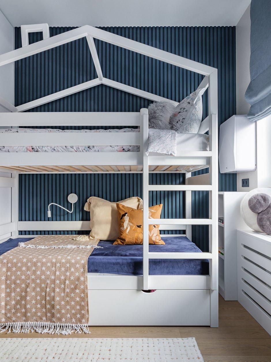 Акцентная стена за кроватью в детской — гипсовые панели, покрашенные синей краской. Еще одно интересное решение в детской: напротив рабочего стола использовали белые стеновые панели LEGO. Это идея заказчицы, интересный декоративный и функциональный прием.