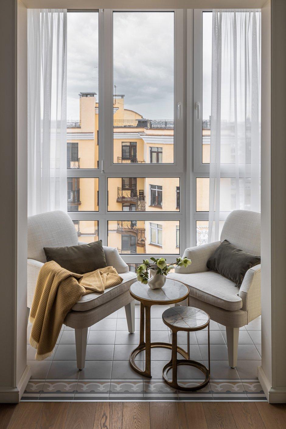 Балкон утеплили, положили плитку. Для зоны отдыха выбрали пару одинаковых кресел со светлой обивкой и комплект кофейных столиков со столешницей из камня.