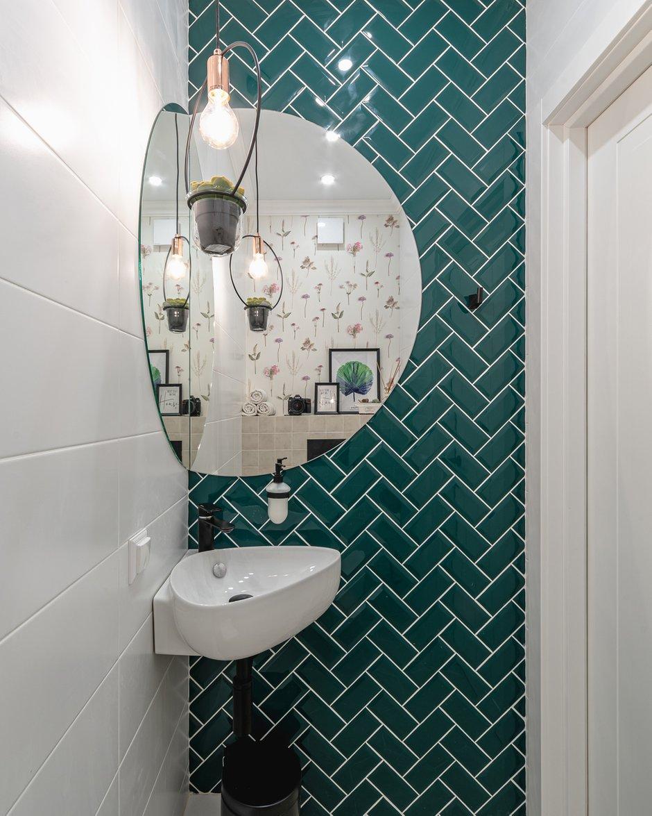 Гостевой санузел оснащен интересной угловой раковиной и гигиеническим душем.