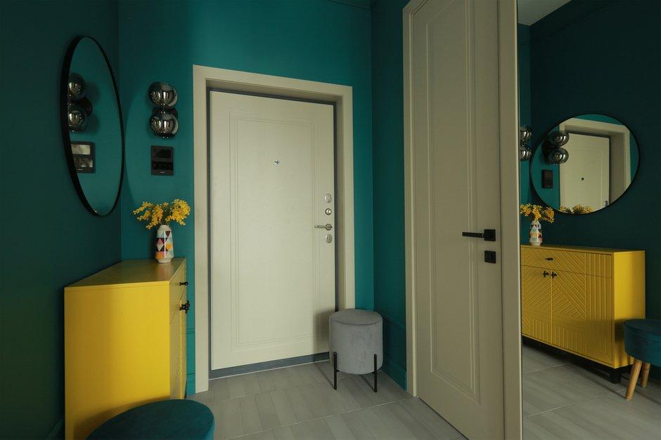 В прихожей на стене напротив гостиной появилось зеркальное панно из серебряного и бронзового зеркал: оно увеличивает освещенность прихожей, создает иллюзию каскада из подвесных светильников с красивыми сине-зелеными плафонами, добавляет красочность коридору благодаря отражению в нем гостиной.