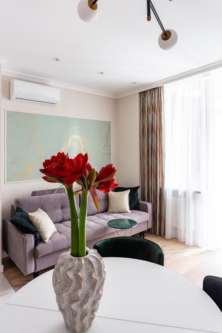 Лиловый диван и фреска красивого зеленого оттенка отлично смотрятся вместе.