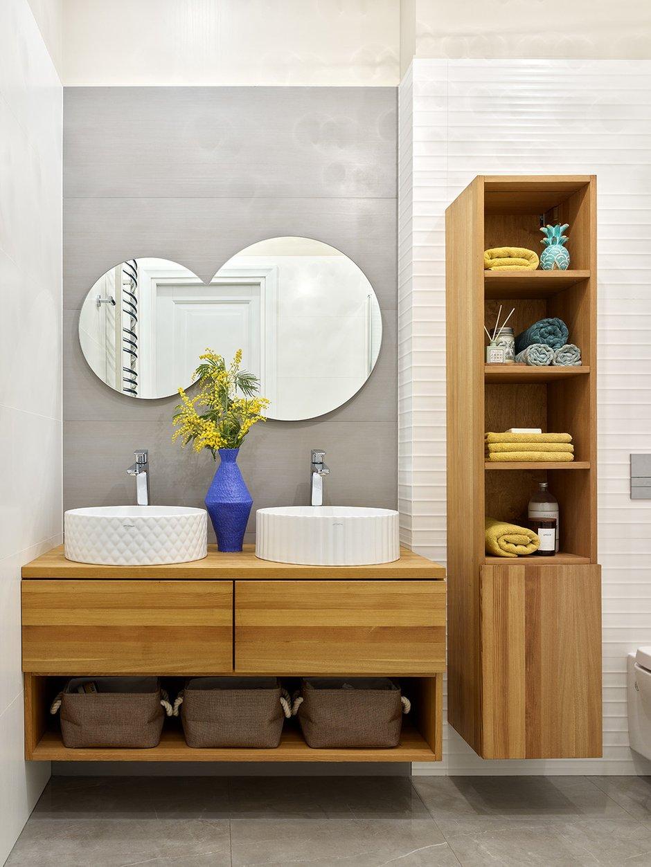 Подвесная тумба и пенал из лиственницы (влагостойкая древесина) сделаны по чертежам дизайнера. Две разные по орнаменту, но одинаковые по размерам накладные раковины вносят разнообразие и несерьезность в интерьер. Продолжает тему «сросшееся» двойное зеркало, подсвечивающееся по периметру сзади.