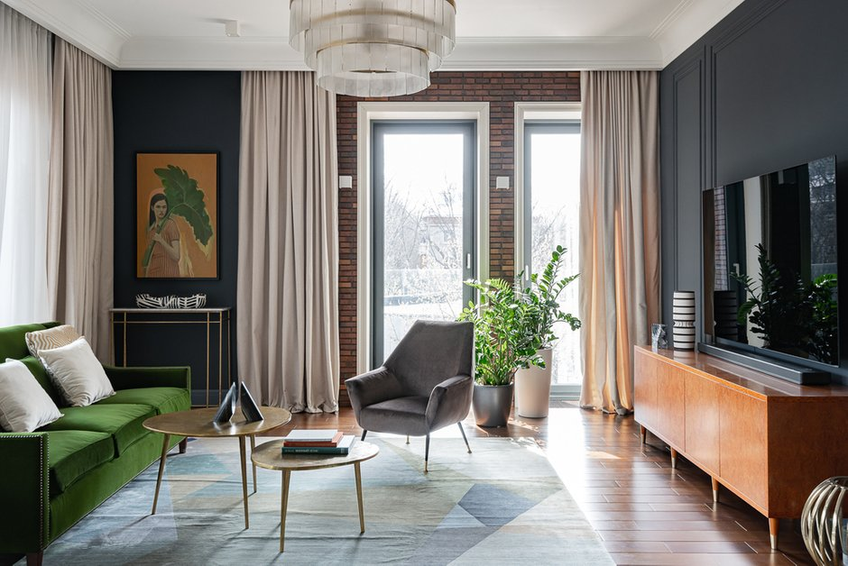В гостиной зоне отлично сочетаются штукатурка графитового цвета и имитация кирпичной кладки. Для контраста выбрали светлые гардины.