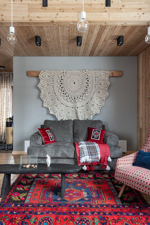 Еще один уютный уголок в гостиной. Разнообразие текстиля: диван, покрывала, ковер на стене и ковер на полу транслируют богатство этнических мотивов, вдохновивших хозяев этого дома. Карниз для ковра сделан из ильма с соединением в японском стиле.