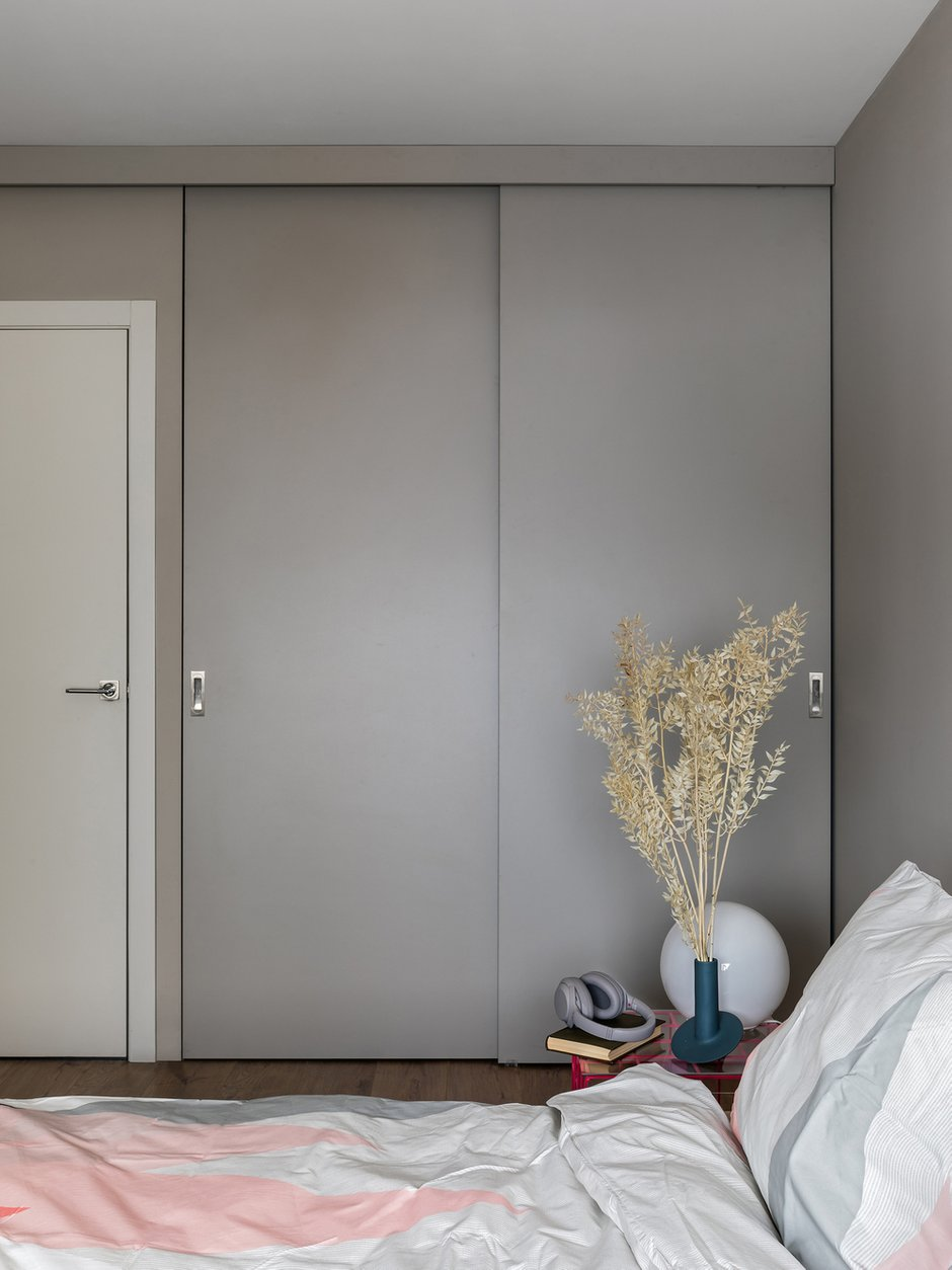 В спальне стены под покраску, в таких же оттенках подобрали материал для раздвижных фасадов встроенного шкафа.