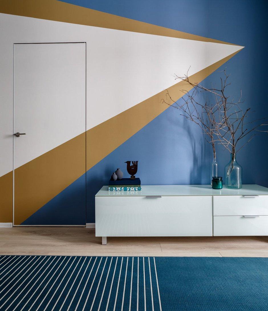 Дизайнеры сделали ставку на яркие синие и сине-зеленые оттенки: одну из стен украшает крупный узор в виде цветных стрелок.