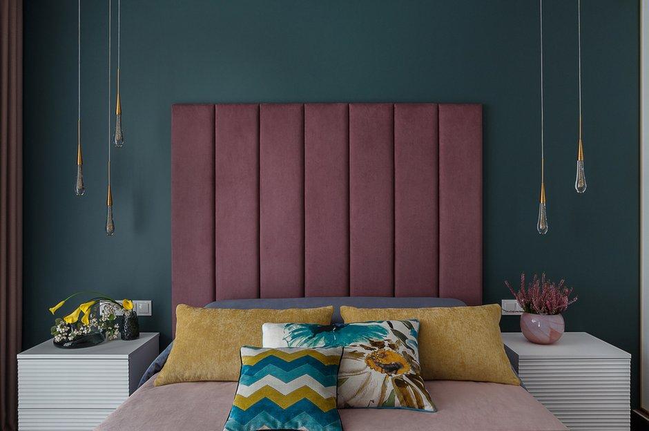 Дизайнер использовала красивое сочетание насыщенного темного цвета стены с изголовьем винного цвета. Яркости добавили с помощью подушек.