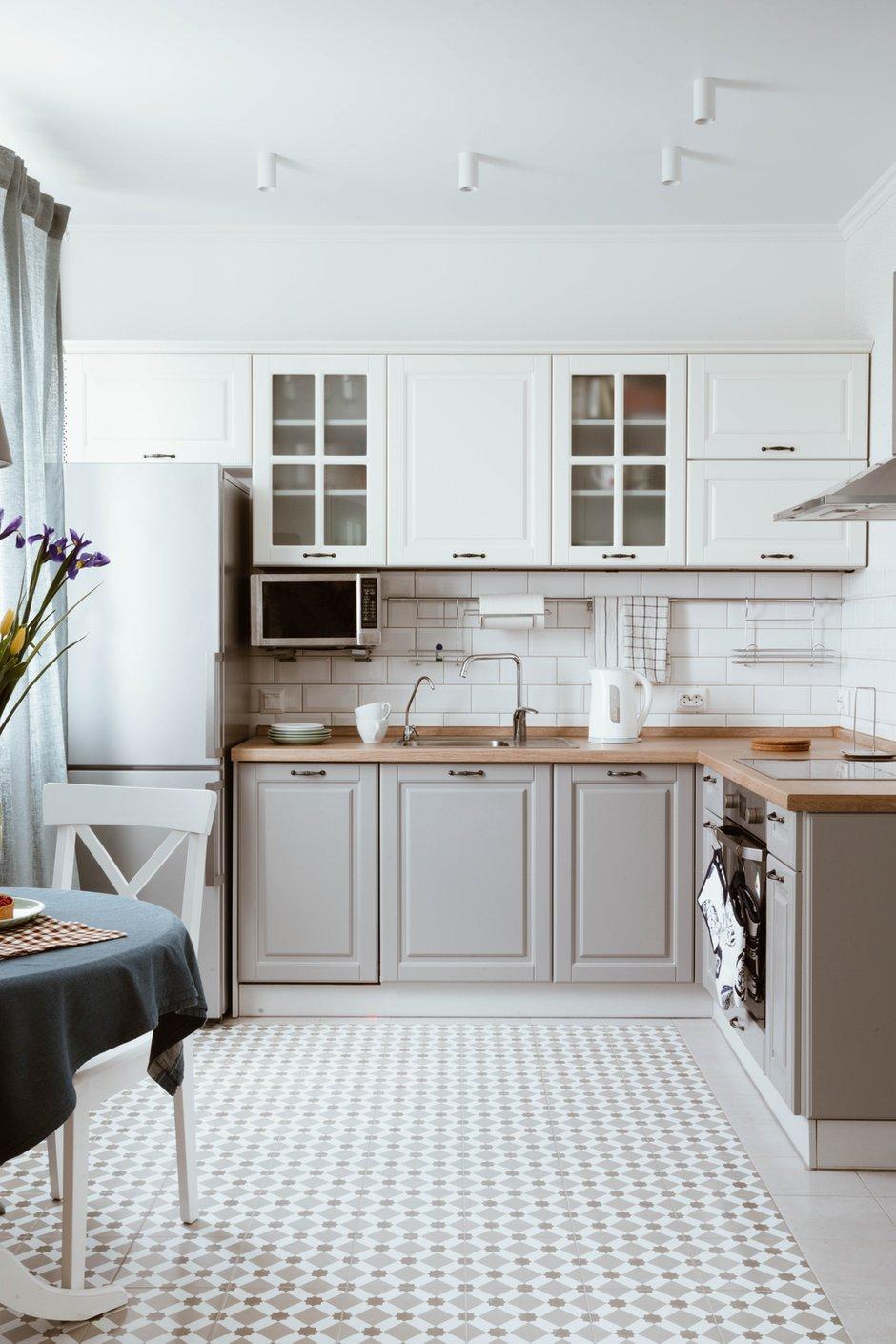 Несмотря на то, что размеры кухонных шкафов спроектировали стандартные, кухню делали на заказ, производство находится в Санкт-Петербурге. Фасады — эмаль двух цветов. Два верхних шкафчика с расстекловкой повторяют распашные двери в комнату.