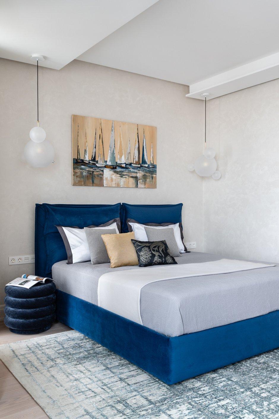 Гостевая спальня оформлена более лаконично. Акцентом стала кровать в обивке насыщенного синего цвета.