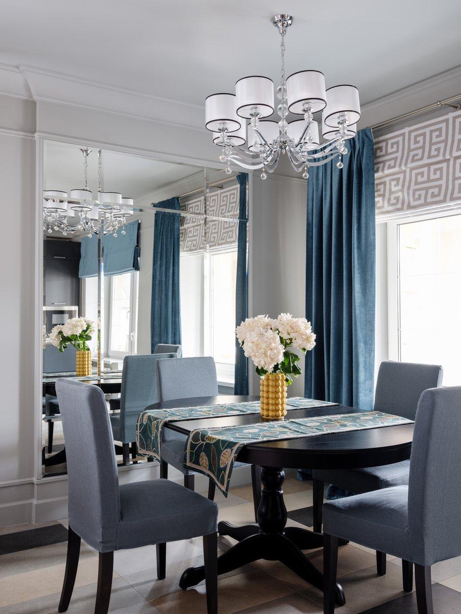 В зоне столовой сделали большое зеркало от пола до потолка, которое разделено на несколько частей, каждая часть с фацетом. Этот прием визуально увеличивает пространство гостиной-столовой и кухни.