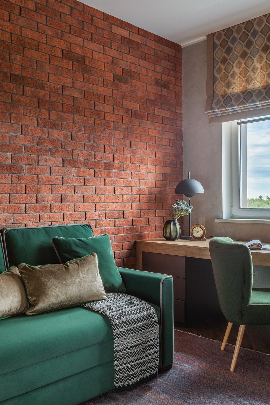Одну из стен в кабинете оформили красным кирпичом. На его фоне особенно эффектно смотрится зеленый диван.