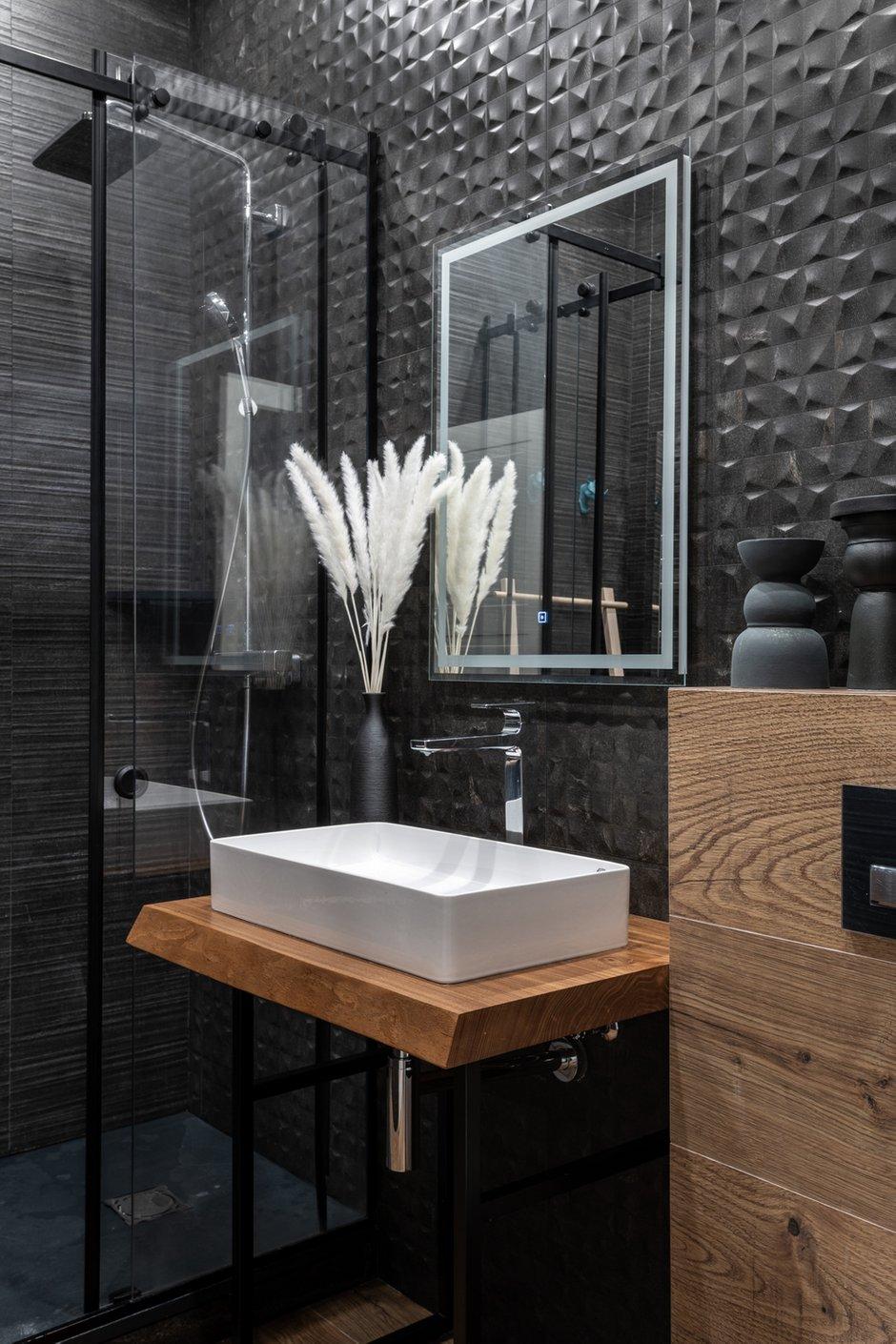 Гостевой санузел — душ со стеклянной перегородкой и плитка в урбанистической стилистике темно-графитового цвета.