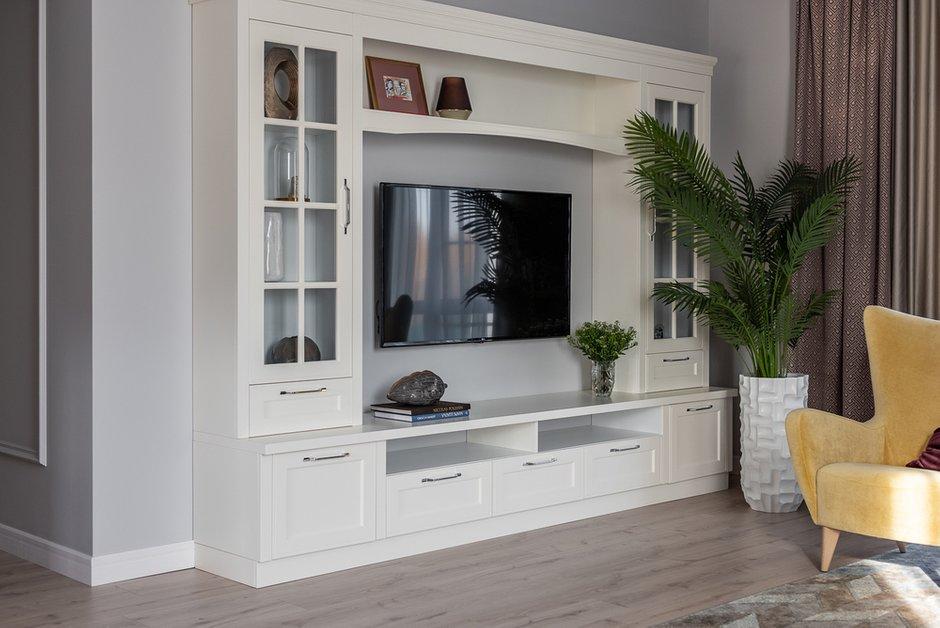 В гостиной за хранение отвечает стеллаж с телевизором, изготовленный по индивидуальному заказу.