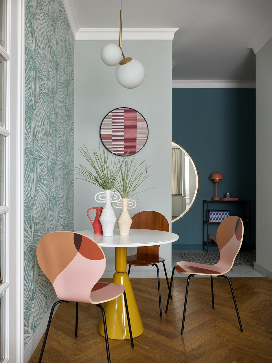 Цветные принты полукругов на стульях поддерживаются выглядывающим полукругом зеркала в прихожей.
