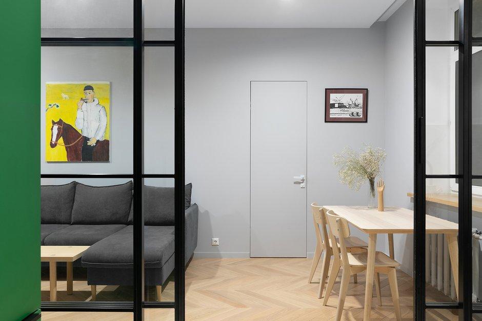 Было использовано минимальное количество отделочных материалов — керамогранит, паркет и серый нейтральный фон декоративной штукатурки, чтобы дополнительно визуально объединить пространство в небольшой по габаритам квартире.