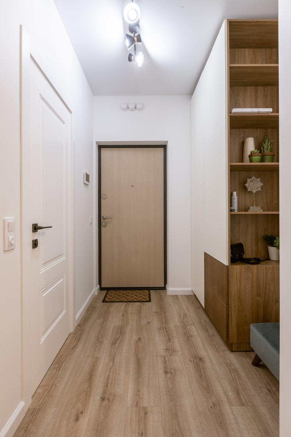 В прихожей есть вместительный шкаф для верхней одежды со встроенными в него открытыми полками, где расставили растения и предметы декора. Это создает ощущение уюта.
