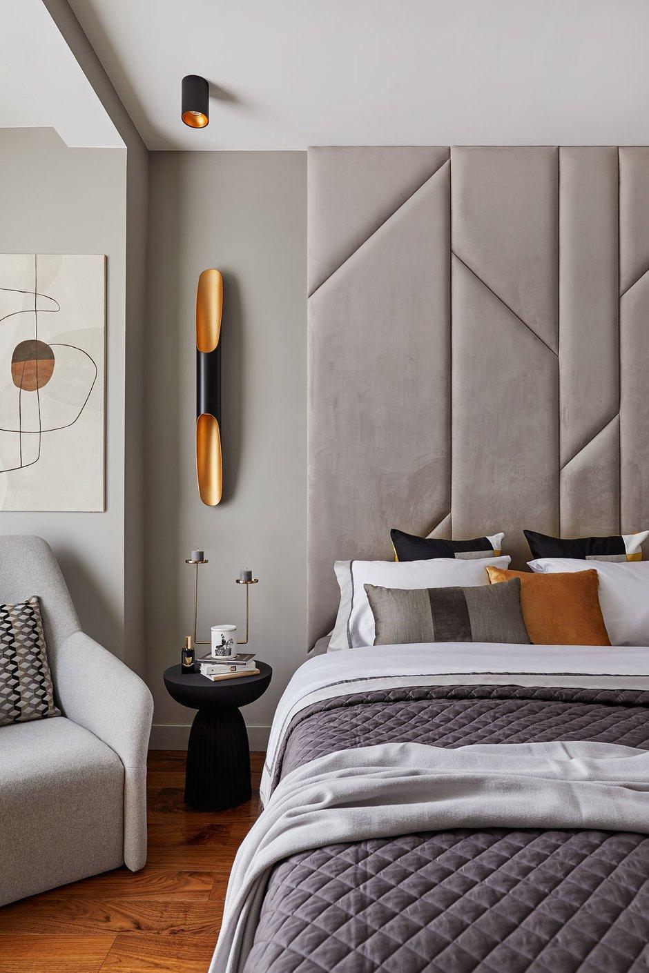 В спальне изголовье кровати выполнили из мягких панелей. Черные и золотые элементы добавили динамики и контраста, сделав пространство более фактурным.