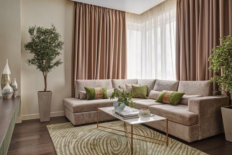Угловое окно подчеркнули диваном такой же формы. А напротив предусмотрели большой телевизор на поворотном кронштейне.
