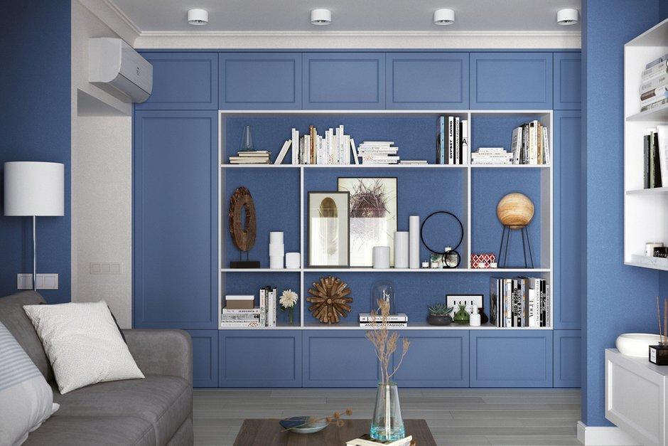 Шкаф-стеллаж установили в проходной зоне гостиной. На синем фоне контрастными белыми линиями выделяются открытые полки с книгами и декором.