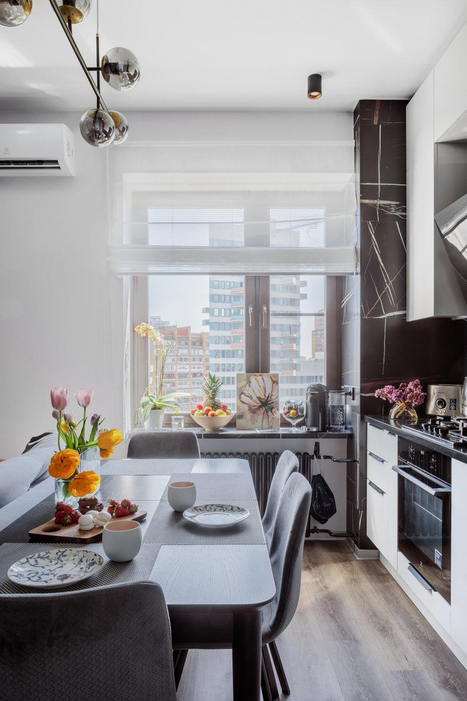 В кухне подоконник выполнен из керамогранита — на самом деле это лестничная ступень. Керамогранит дальше идет по порталу окна и по стене за кухней.