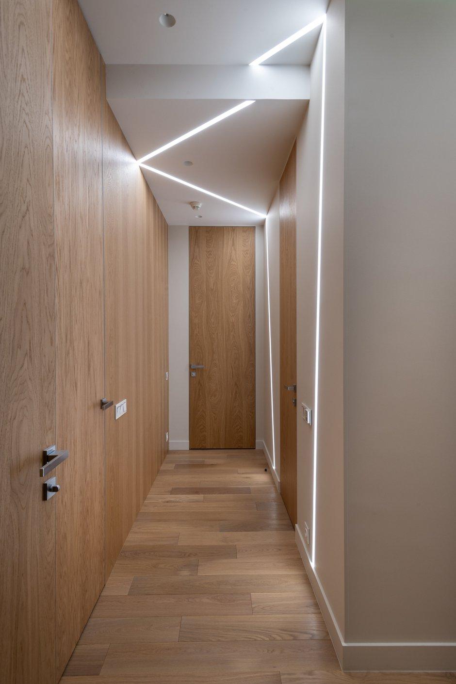 Чтобы подчеркнуть высоту потолков и обыграть длинный коридор в холле, на стене расположили деревянные панели со скрытыми дверями, ведущими в комнаты.