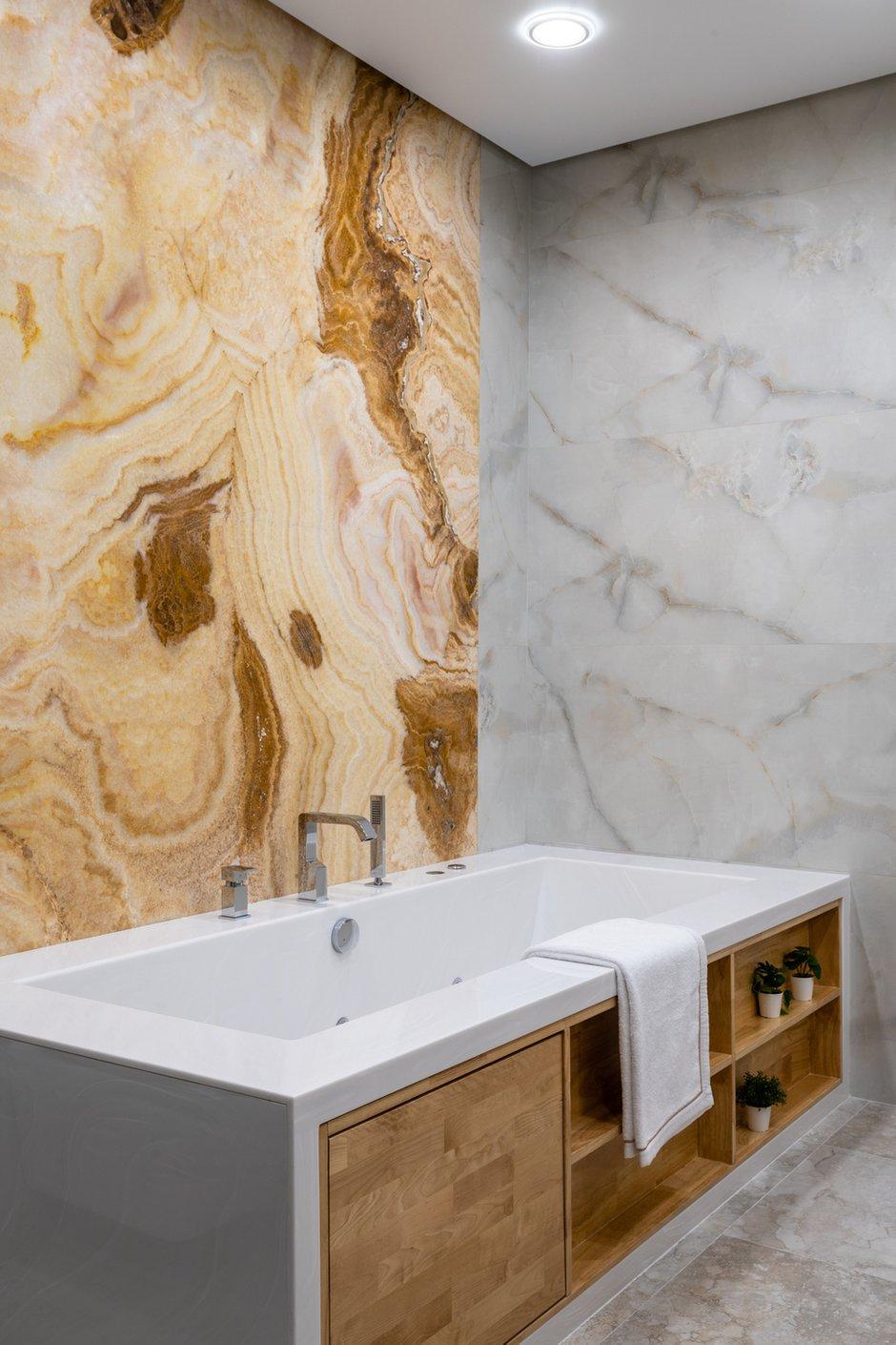 Ванная комната в этой квартире сейчас одно из любимых мест отдыха. Когда выключается основной свет и включается подсветка оникса, пространство становится не просто ванной комнатой, а красивой SPA-зоной. Сама ванна и мебель были изготовлены на заказ.