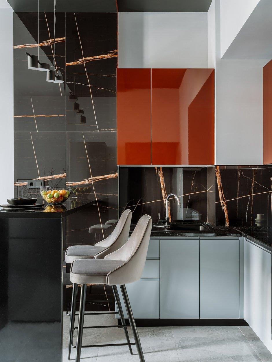 Цвет терракотовых, огненных линий на широкоформатном керамограните стал акцентным для кухонного гарнитура и для оформления стены в обеденной зоне методом color-blocking.