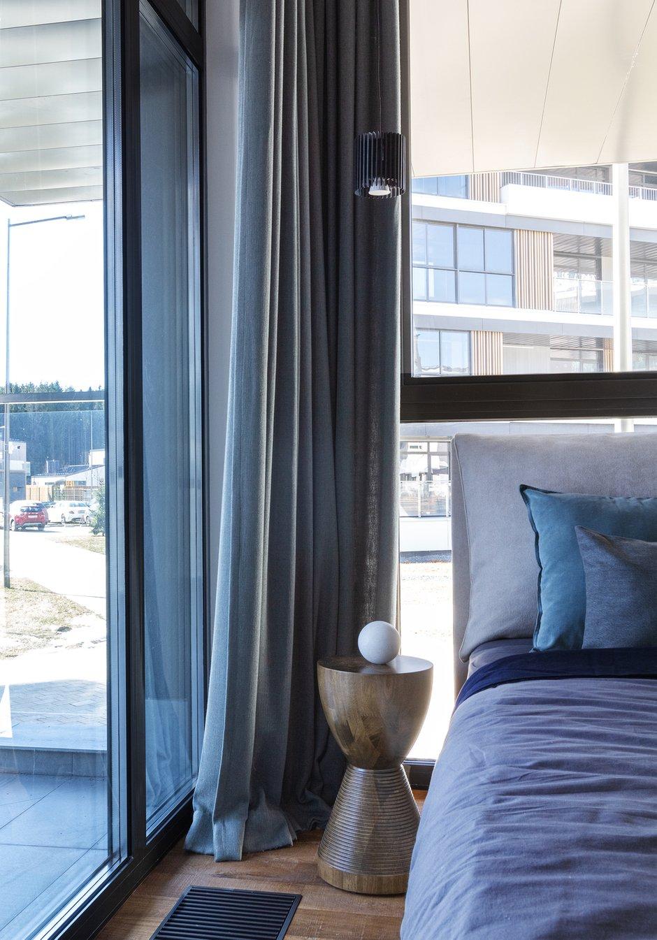 Кровать была просчитана до миллиметра и сделана на заказ. Один их прикроватных столиков напоминает тамбурин, другой — высокий деревянный табурет.