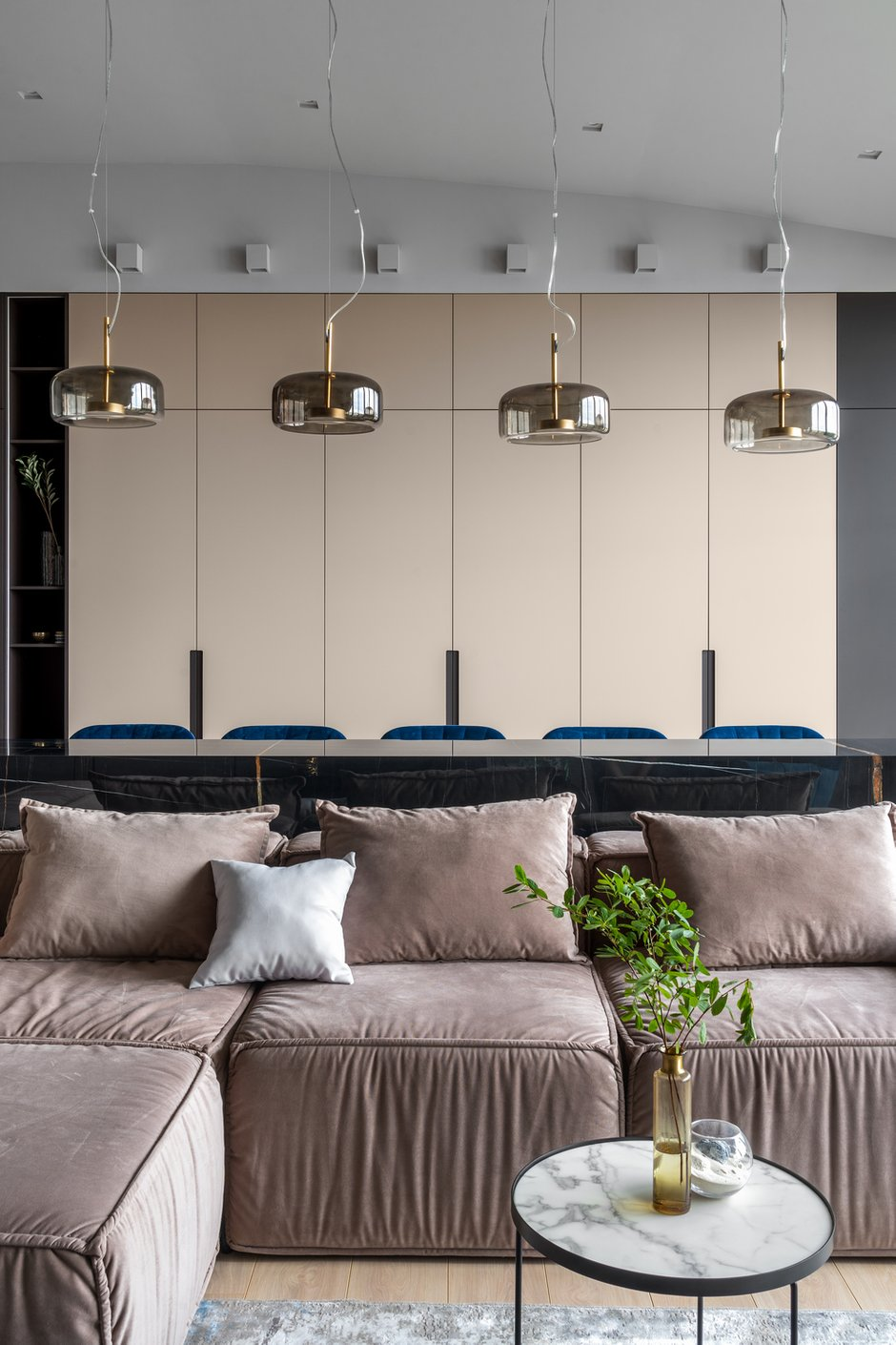 Практически вся мебель изготовлена на заказ. Шкафы сливаются со стеной и играют роль общего фона пространства. По центру гостиной расположили каменный остров, он заменяет обеденный стол.