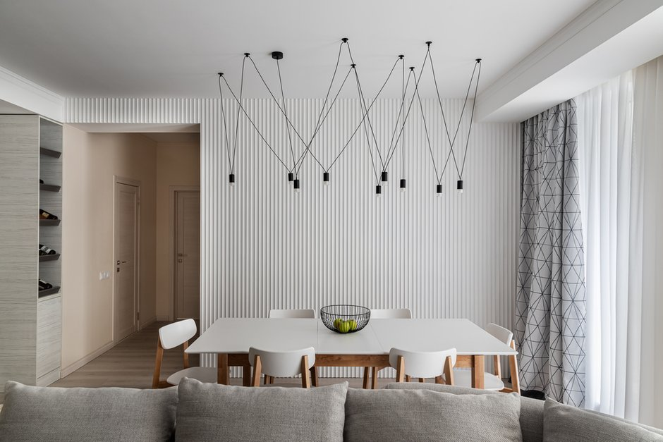 Гипсовые панели сделали интерьер интереснее. Они отлично сочетаются со светильником над столом.